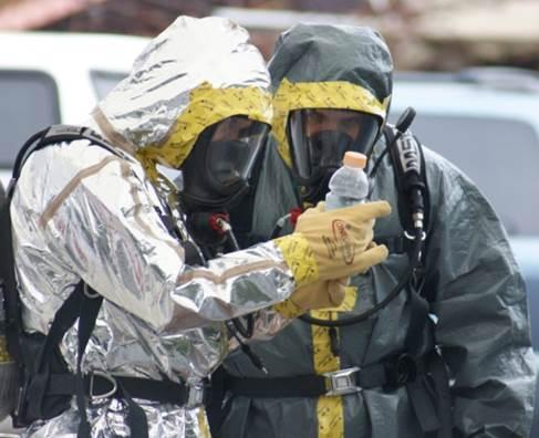Two hazmat professionals holding a one pot meth lab in a plastic bottle.